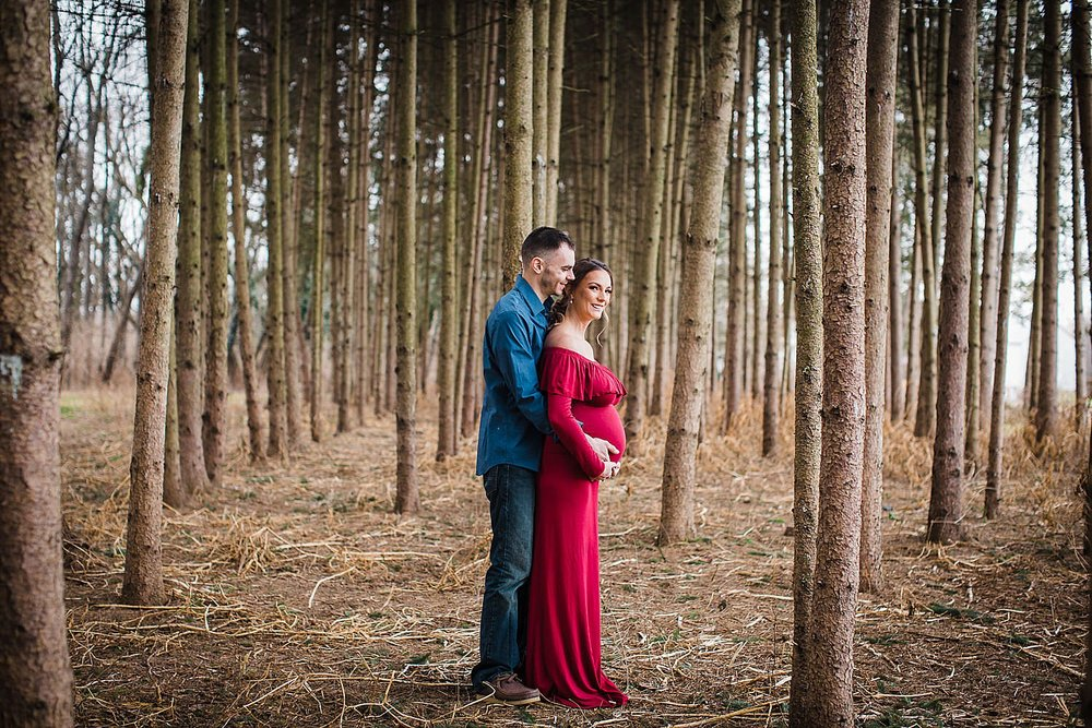 Photo of a young couple standing in a pine forest and the woman is pregnant.
