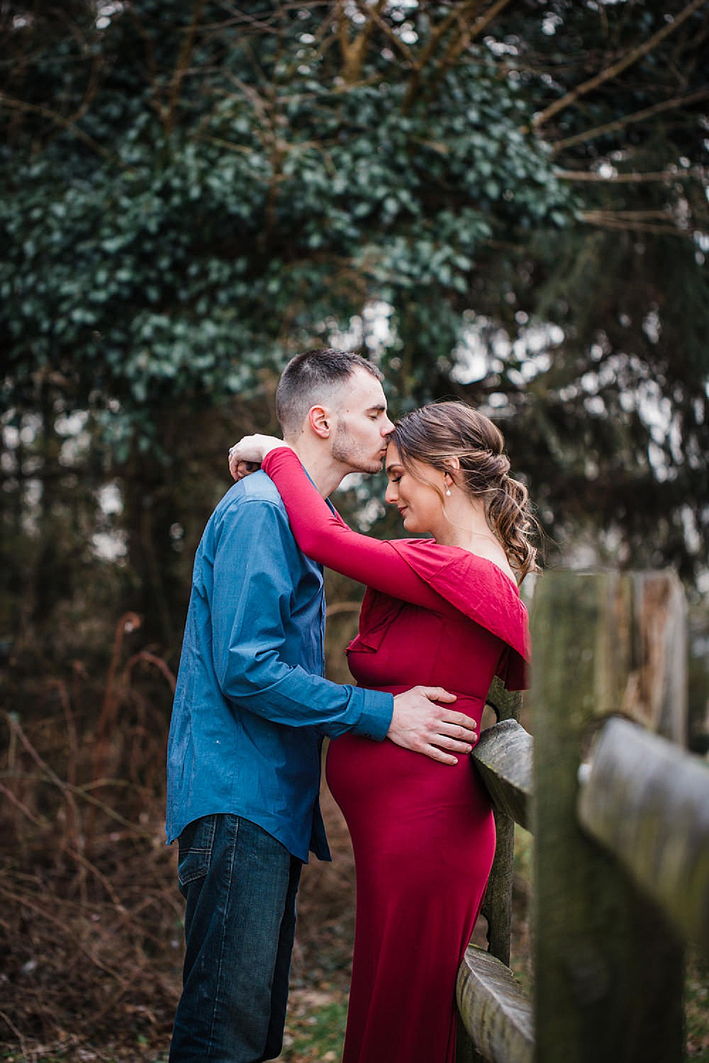 Photo of a pregnant woman in a red dress with her arms wrapped around her husband.