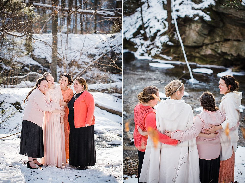 Photo of four young women in long gowns standing in a wintery forest.