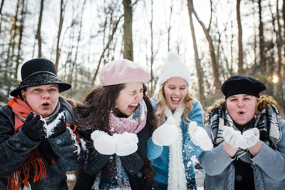 Photo of four young women standing in a row laughing in a wintery forest.