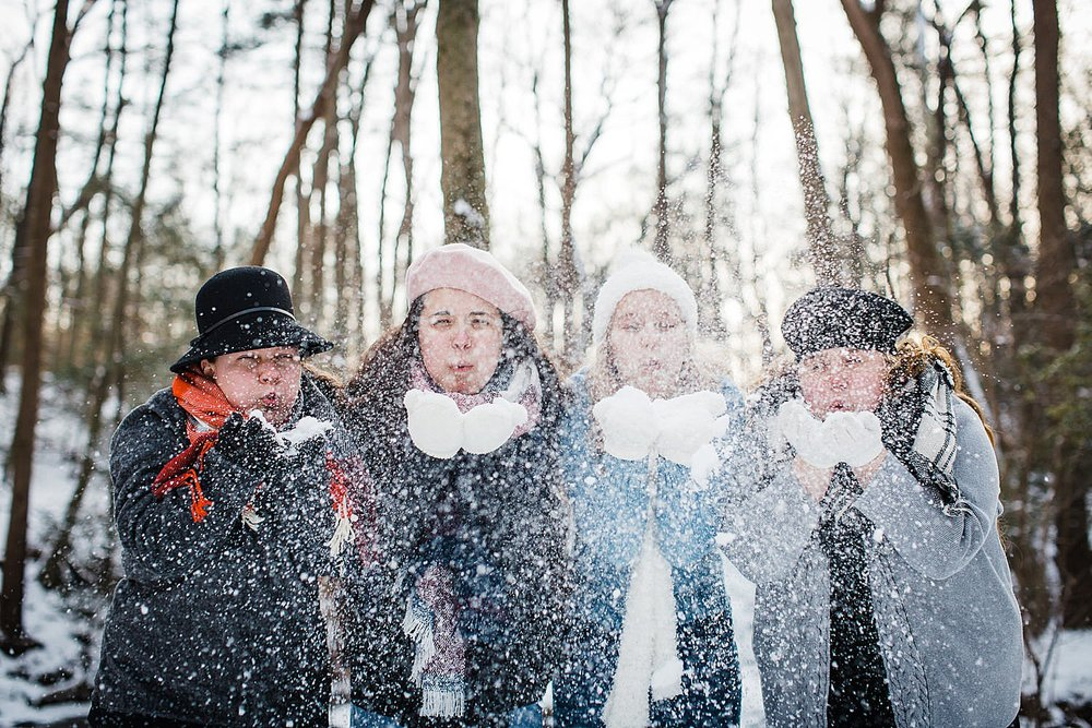 Photo of four young women blowing snow in the air in a wintery forest.