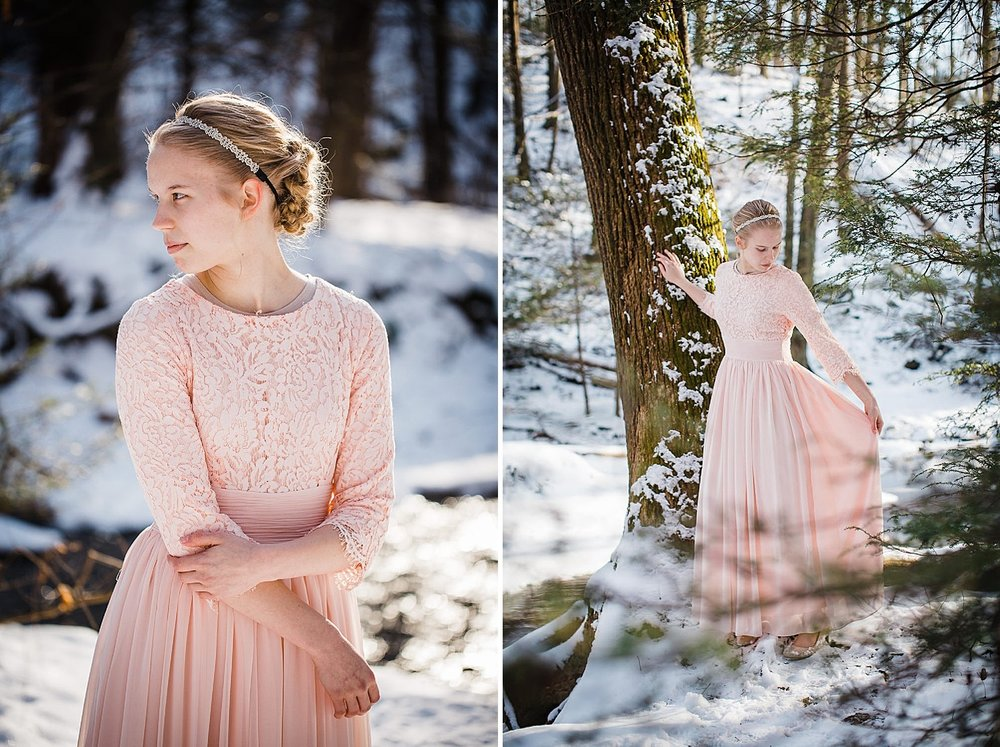 Photo of a young blonde woman in a pink gown standing in a wintery forest.