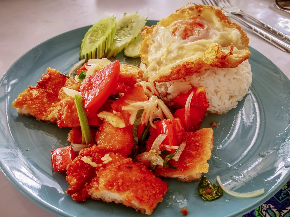 Khao Yam spicy chicken with rice and egg on top - kind of a breaded chicken escalope with veggies in a sweet and sour sauce