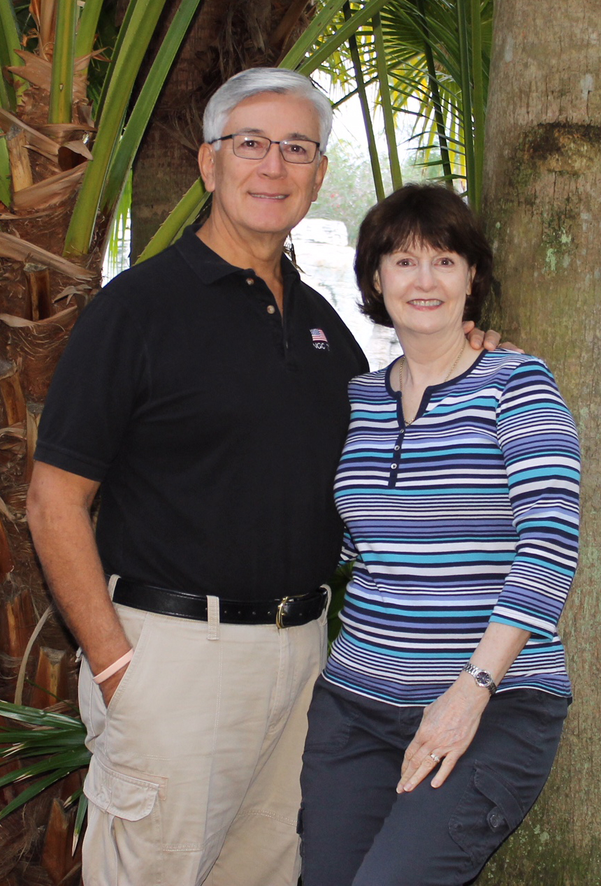 Husband and wife, Vince and Debbie Collier, pose for a picture in front of palm trees.