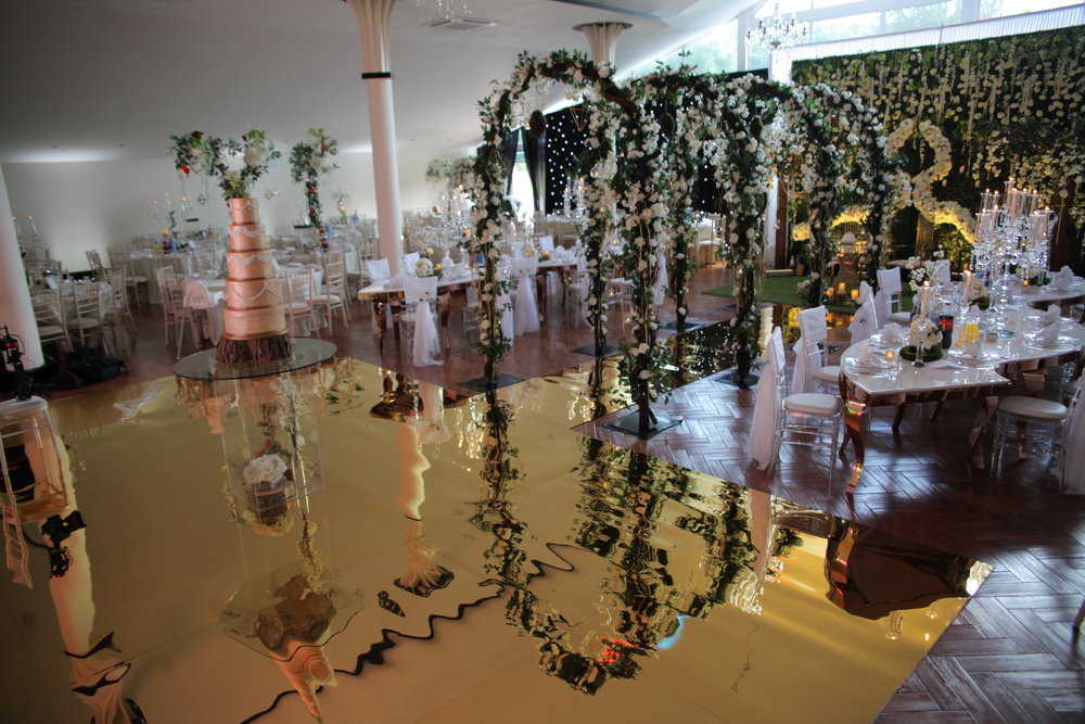 The Dancefloor - We custom built a lavish Gold Mirror Dancefloor, which had a golden walkway leading directly to the head table, surrounded by the bespoke Family Tables either side.