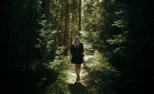 lady walking through a forest path.jpg
