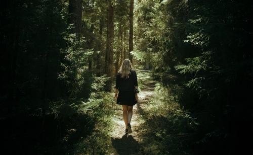 lady walking through a forest path.jpg