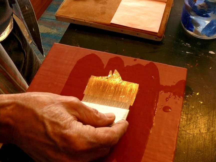 Laying the Gold Leaf - With aid of a gilder's tip, gently lay the leaf onto the surface and allow the gold to float on the water. As the water continues to soak into the Sinopia Clay Bole, the leaf will be drawn down onto the surface.Watergilding can only be performed with surface gold, that is not adhered to a transfer sheet, as gold is in patent leaf.