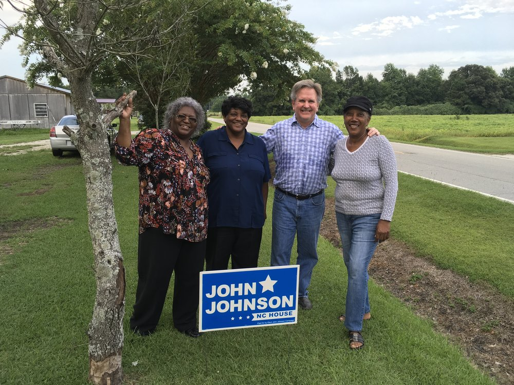 The Corbetts and friends join John in a photo during a walk in the neighborhood in Atkinson