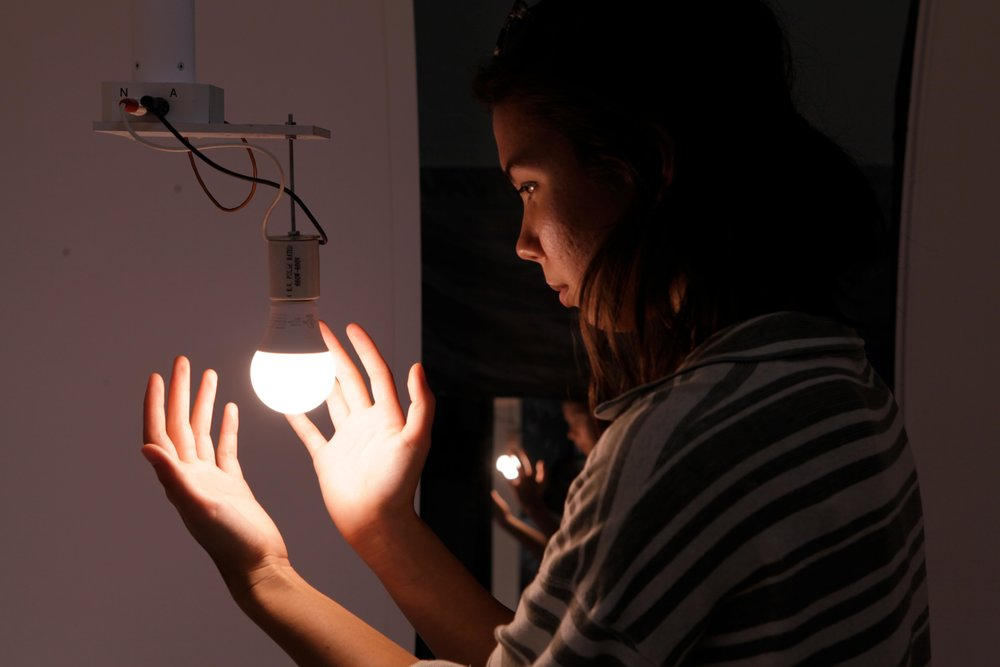 A young female university student wrapping her hands around an LED light bulb attached to a goniophotometer..jpg