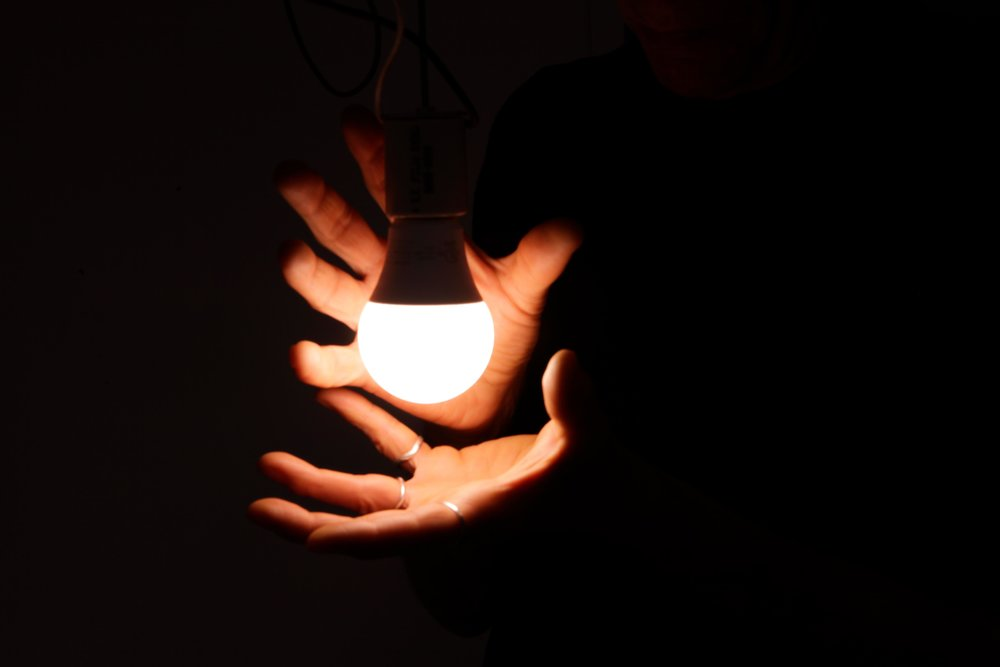 Hands are wrapped around a light source that is attached to a goniophotometer..jpg
