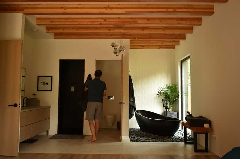One of the goals for Denise and Eric Antonini was to design a bedroom that doubled as a sanctuary. The solid rock bathtub to Eric's right accents the bathroom that opens to the master bedroom.