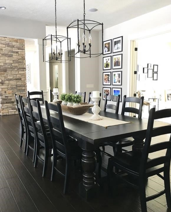 Modern farmhouse dining room with oversized chandeliers and floor-to-ceiling family gallery wall.