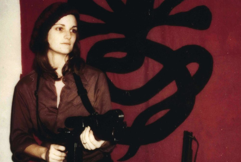 Patty Hearst posing in front of SLA banner
