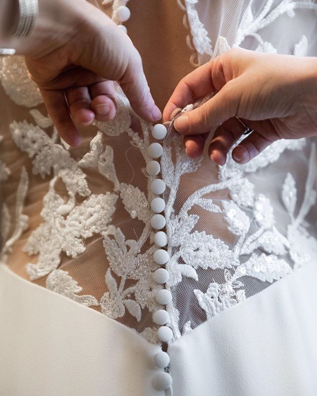 #tuestip When purchasing a gown with buttons, be sure to have the person helping you get ready do it a couple times before your wedding day or you might end up running behind schedule😭 . A dress with more than a dozen buttons can be time consuming, and if one is skipped you'll have to do it all over again when you finally realize it at the very top and you've got one extra 🙄 . Hidden zippers make it easier not to miss a button, but you still have to button each one individually so make time for it😍 . . Better yet: let me help you with that and you won't have to even stress about it at all 😉 #shamelesspromotion #justmakeitfun #dopeaf . . 📷 @adrian_etheridge_photography  Salvage Station Full Vendor Team: Venue: @salvagestation| Wedding Dresser/Styling & Coordination: @justbloomtogether Photographers: @sheilamraz.photography & @adrian_etheridge_photography |Dress Boutique: @weddinginspirationsbridal| Tuxes, Men's Shoes, Bow Ties: @mitchellstuxedosavl| Rings: @rhodesweddingco| Jewelry: @robinleeessentials| Hair: @grateful_sunshine| Makeup: @traciepotillo_mua | Videographer: @benavidesvideography| Invitation Suite: @that_joy_design| Macrame: @kindredcompanygoods| Cake: @828sweetevents| Florals: @stargazersdesigns| Drapery: @charlesjosefbridal| Linens: @carolinaloveevents| Rentals: @eastwestvintagerentals& @vintage_indigo_rentals| Models: @mrvancott& @ballzac1, @lkazmarekart& @atlbraves91p . . #weddingdresser #fashiontips #weddingplanningtips #weddingtipsandtricks #tuesdaytips #personalstylist #buttons #illusionlace #designerweddingdress #adrianetheridgephotography #justbloomtogether