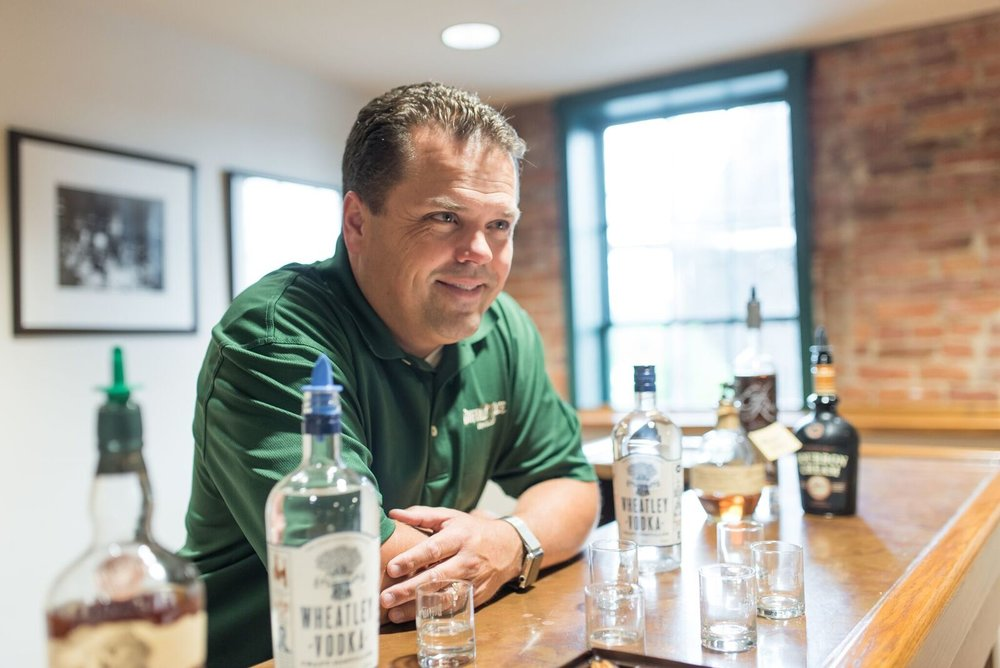 Harlen Wheatley standing at a bar smiling, surrounded by Buffalo Trace products, including Wheatley Vodka.