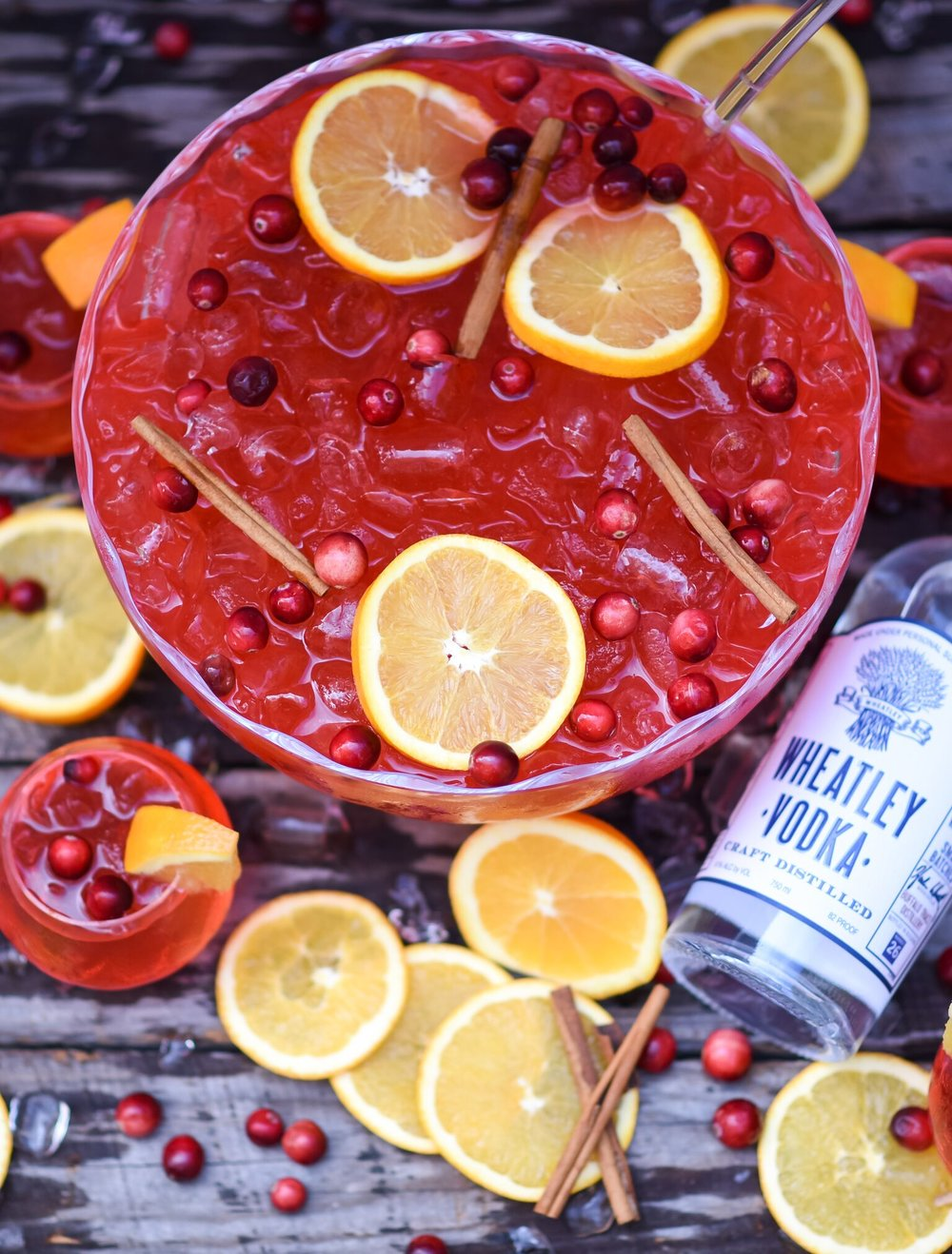 Overhead shot of a bowl of punch with orange slices, cranberries, cinnamon sticks and a bottle of Wheatley Vodka.