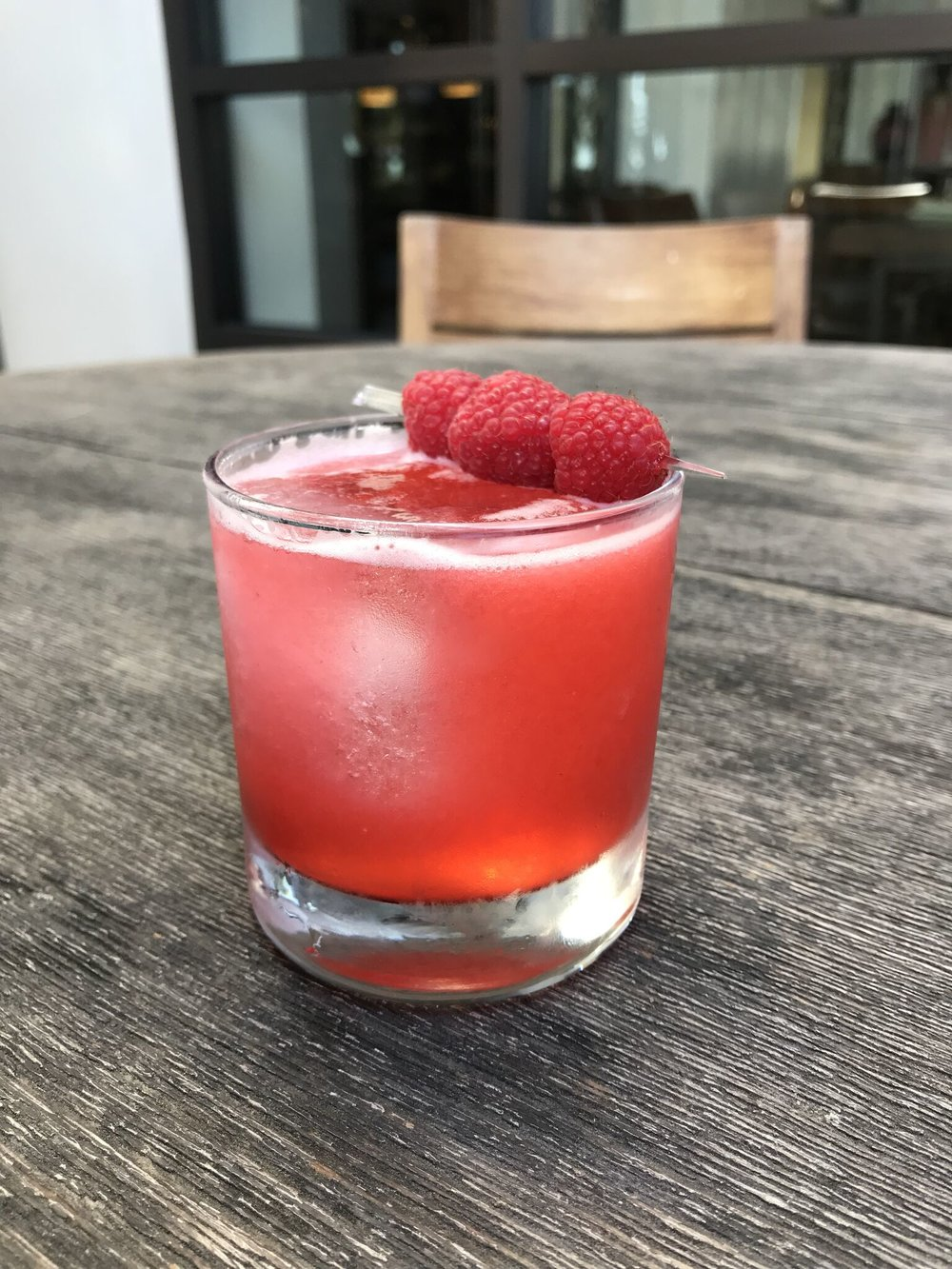 A raspberry colored cocktail sitting on a table.