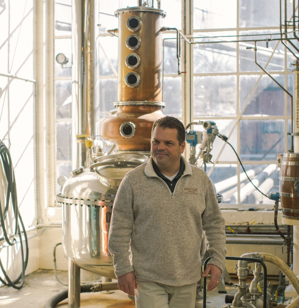 Harlen Wheatley standing in front of his custom-built, one of a kind copper micro-still.