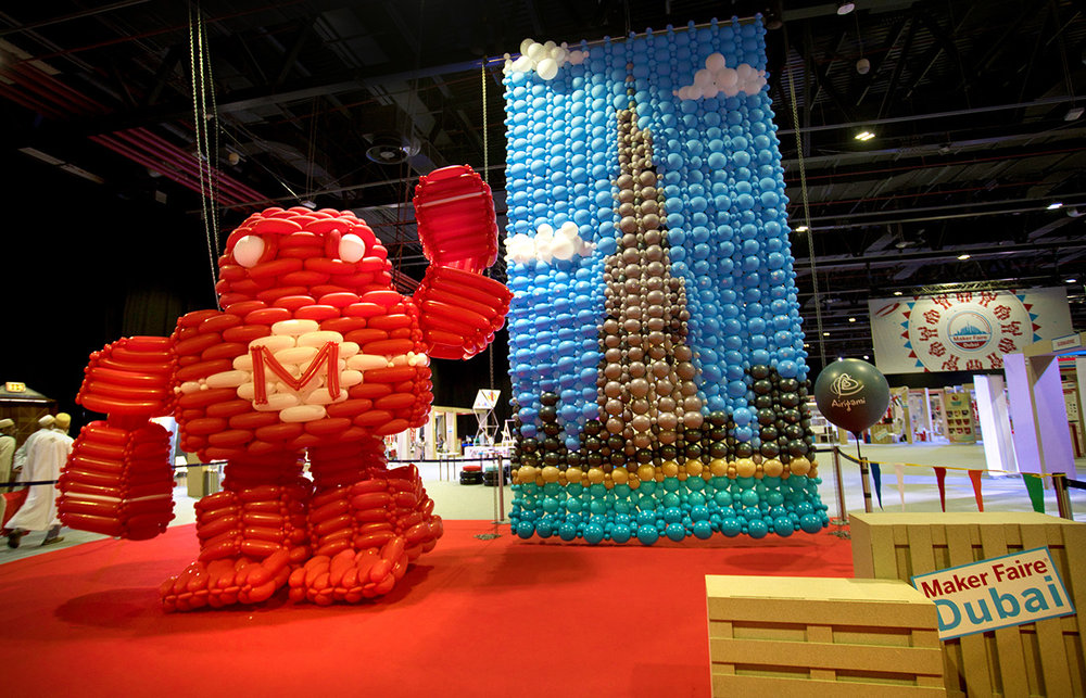 Airigami Makey in front of a Bubble Mural of the Burj Khalifa at Maker Faire Dubai.