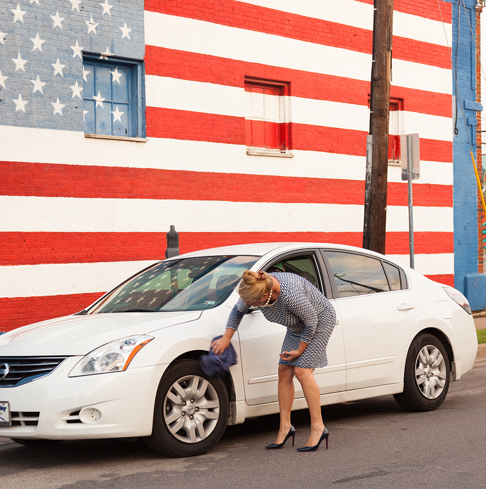 Our founder, Michelle Corson, making sure a client's car is spotless before delivery.