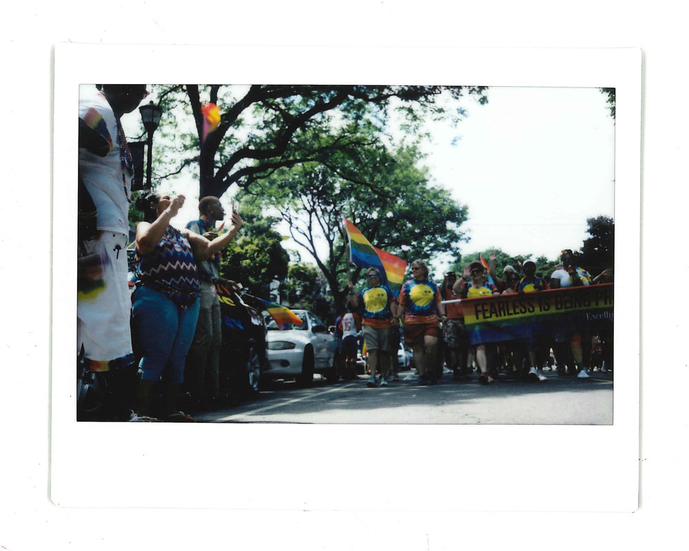 Kim (left) waving her Pride flag as the parade marches down Park Avenue.