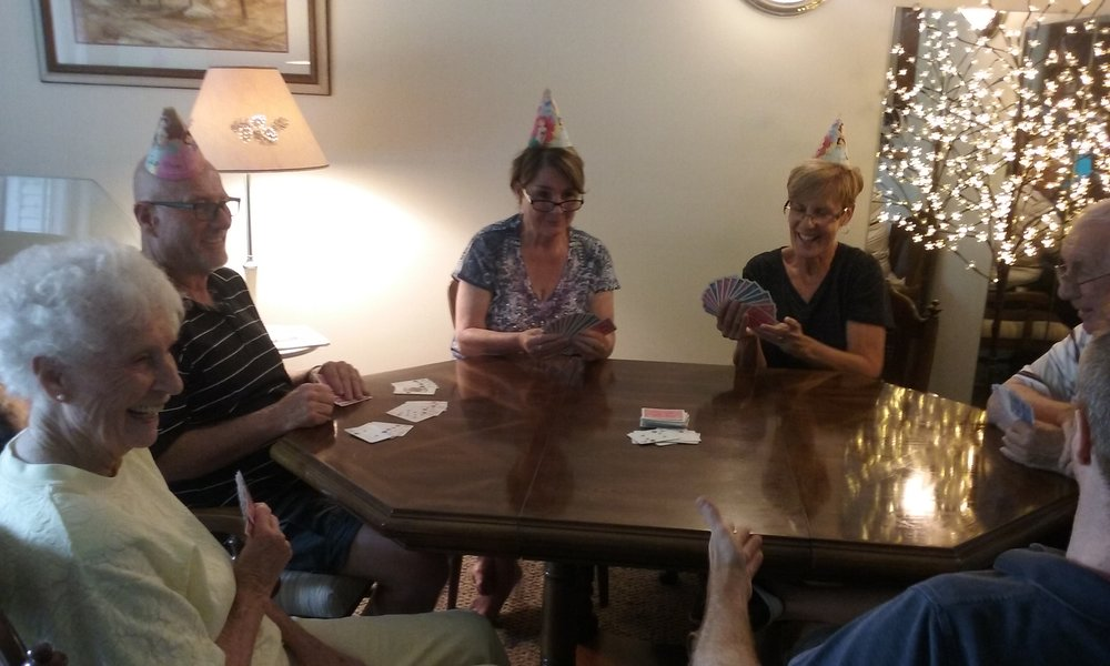 A family gathering, playing the same hands with party hats!