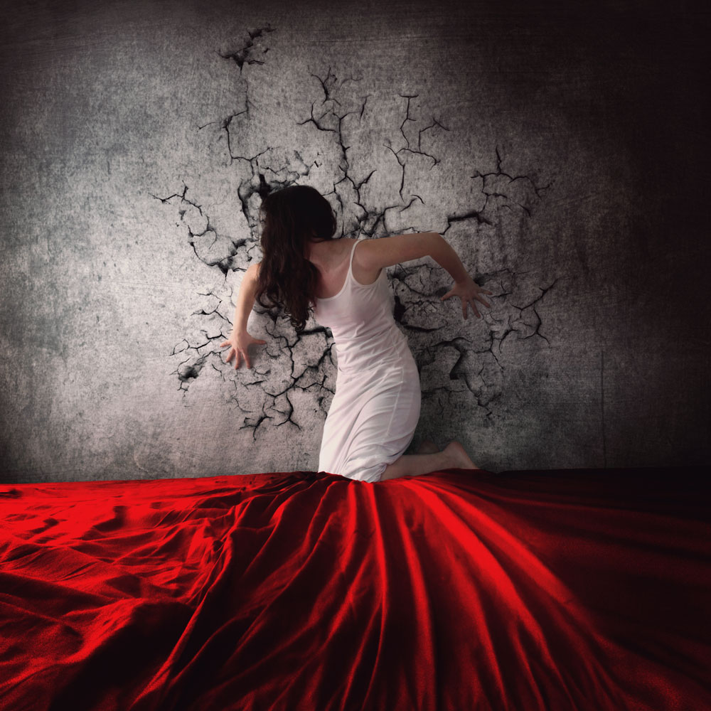 A woman in a white dress with her face covered by hair holds a cracked wall on a red bed
