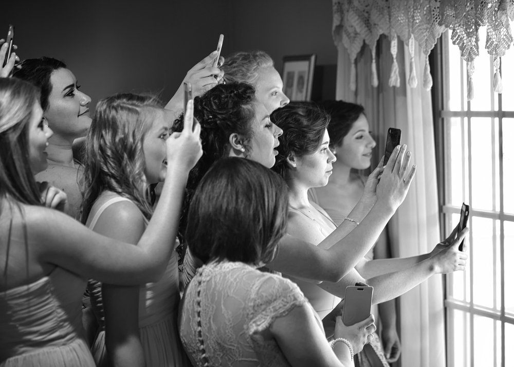 Bridesmaids in a house looking out a picture window at the bride taking pictures with cellphones. Black and white image