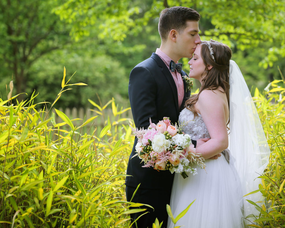 Groom in dark-blue tuxedo kissing Bride in a beaded-corset with a pastel-colored bouquet on forehead outdoors in tall grasses