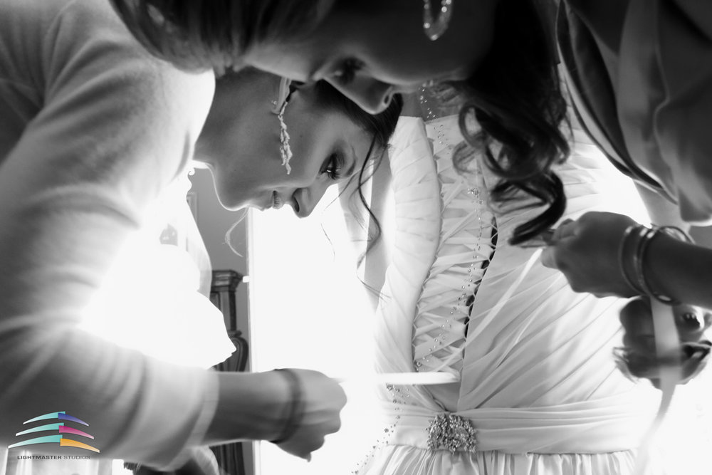 Two Bridesmaids bent over bustling a Martina Liana corset trumpet  wedding dress in black and white image