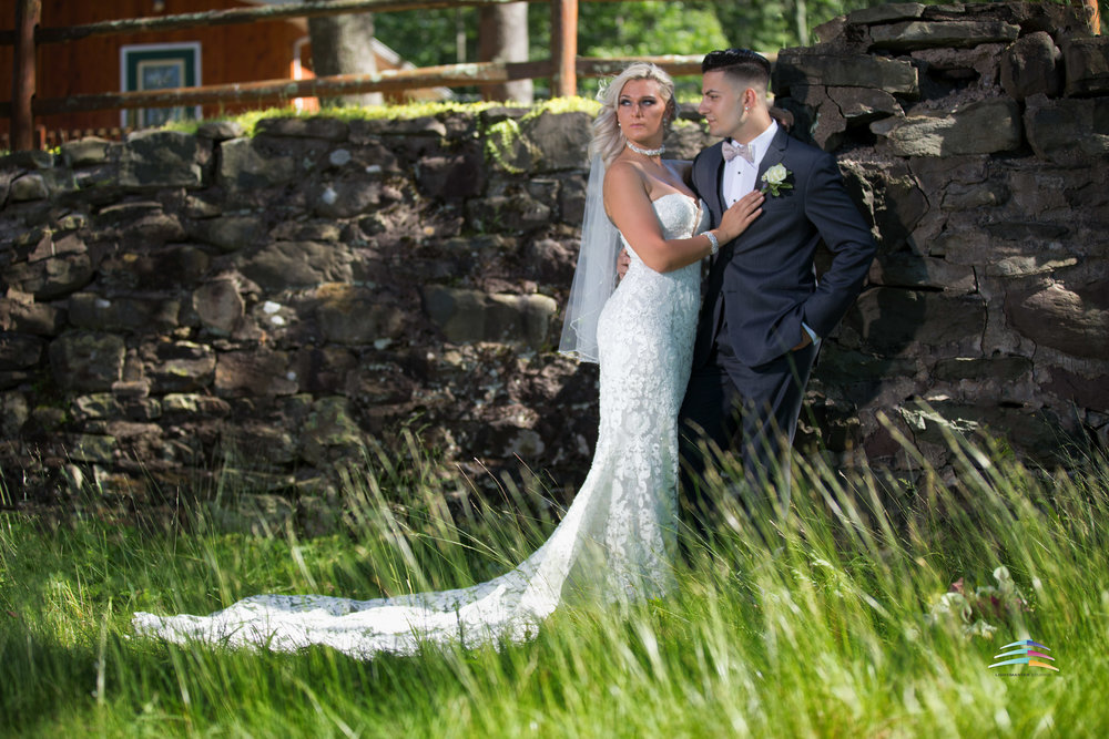 wedding-couple-in-front-of rock-wall-with-blowing-green-white-wedding-dress-form-fitting-and-gray-tuxedo-Trout-Lake-Inn-Summer-Project-Lightmaster-studios-.jpg