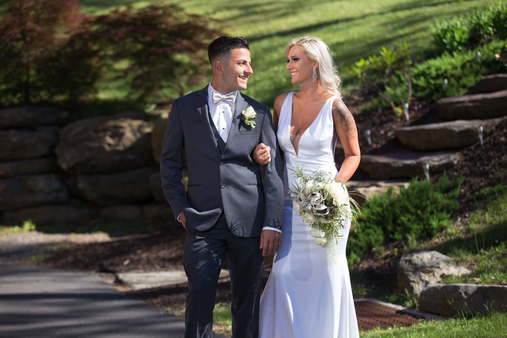 Bride in a White halter top wedding dress with a groom in gray tuxedo smiling and gazing at each other in rustic setting
