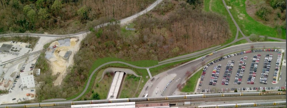 Image of Aerial Photo of Fort Totten Metro Station with commercial trains on both northbound and southbound tracks. Image also features a portion of the Metropolitan Branch Trail located around the outer edge of the Fort Totten Metro Station.