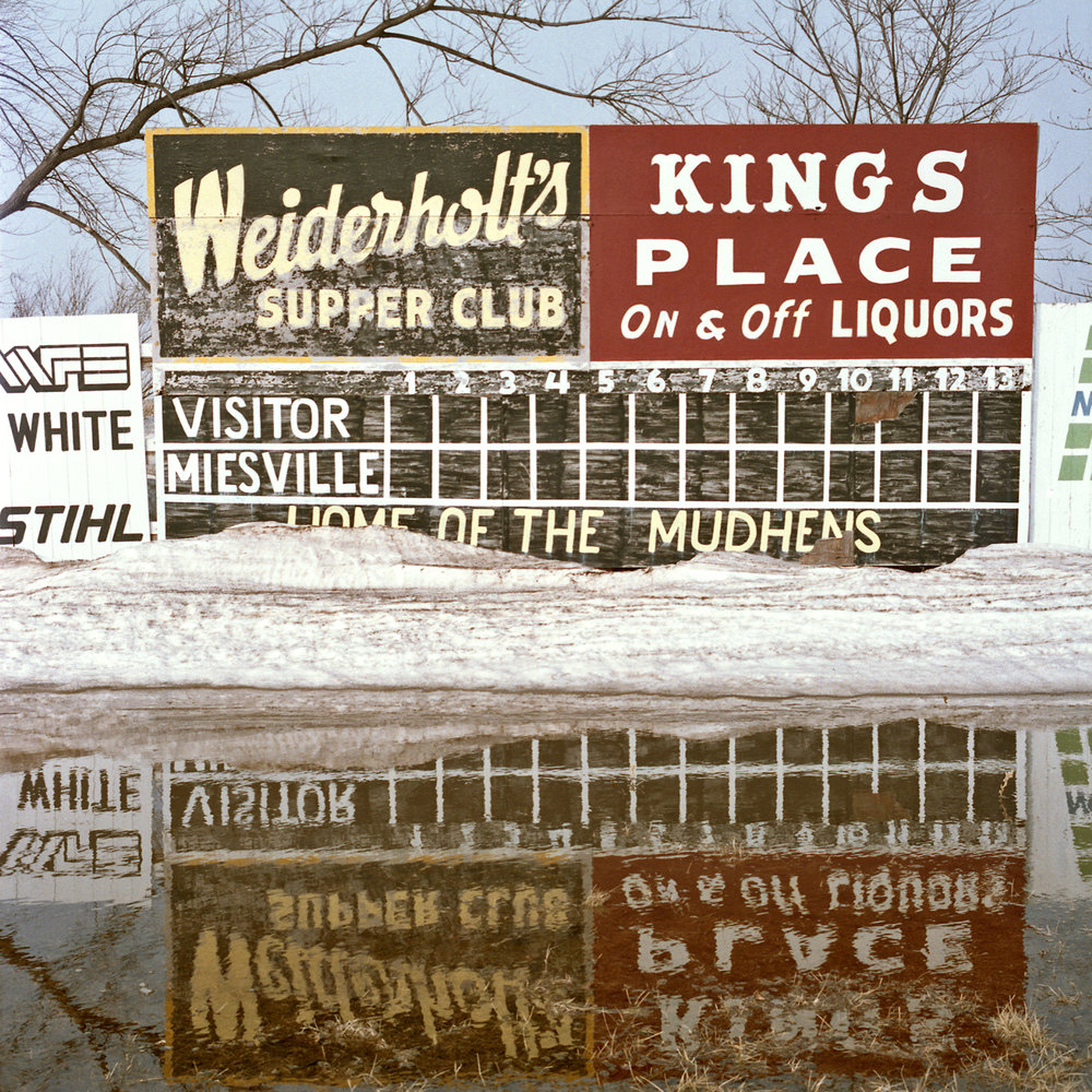 "Miesville Mudhens Field, Minnesota. March 1989. Rural ballpark at the edge of a cornfield known as ""Minnesota's Field of Dreams"" before being spruced up for the season. Several years later, my husband Dan and I celebrated our wedding anniversary with a Sunday prime rib dinner at Weiderholt's Supper Club which has been family-owed for 87 years. I mentioned the special occasion to the wait staff and they surprised us with the gift of a decorated round 9-inch chocolate cake. A WHOLE CHOCOLATE CAKE!"