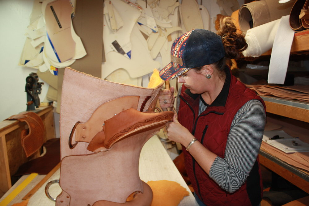 Anderson glues a strip of leather she hand-tooled, adhering it around the edges with a wooden tool.
