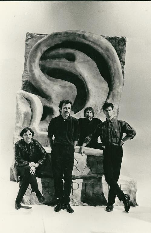 Dave, Hugh, Jet Black, and JJ with the 'ear' sculpture