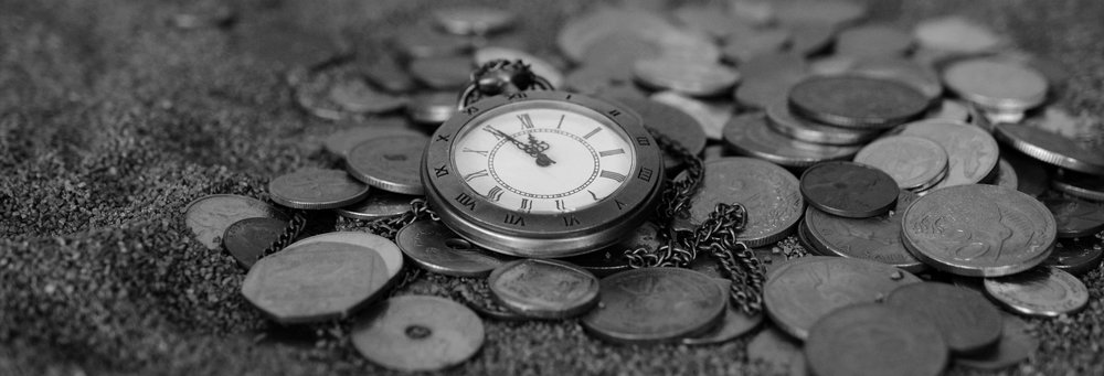 Image of a watch sitting on a pile of coins.