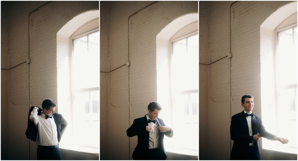jake-kendra-erie-wedding-groom-putting-on-jacket.jpg