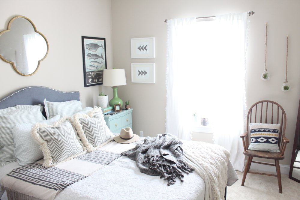 Guest bedroom with blue upholstered headboard and decorative pillows