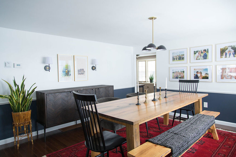 Dining room with handcrafted wood table, chairs and bench seating, gallery wall, white and navy paint colors