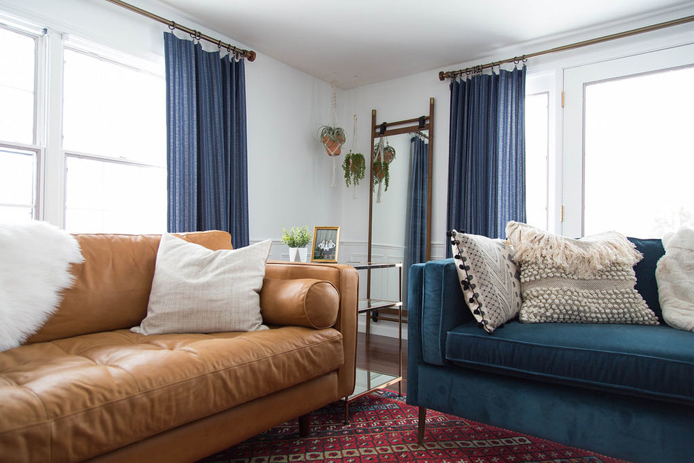Living room with camel leather couch, blue couch, and blue curtains