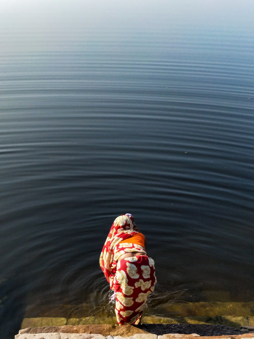 Walking around the Brahma temple, I met a woman sitting beside a lake at sunset with tears rolling down her face.