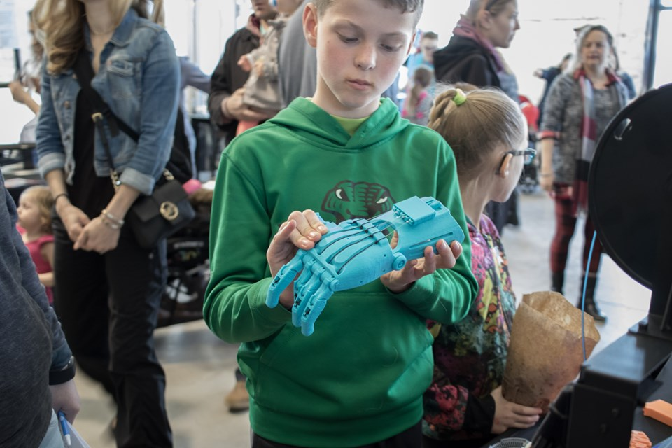 A young man examines a 3D printed hand from the Maker North Inc. exhibitor booth at the Science Carnival on Saturday.  Jeff Klassen