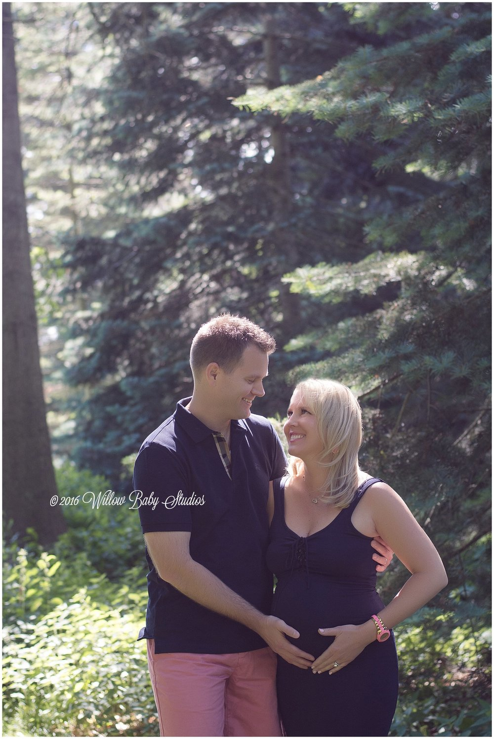 Pregnant-couple-smiling-surrounded-by-trees
