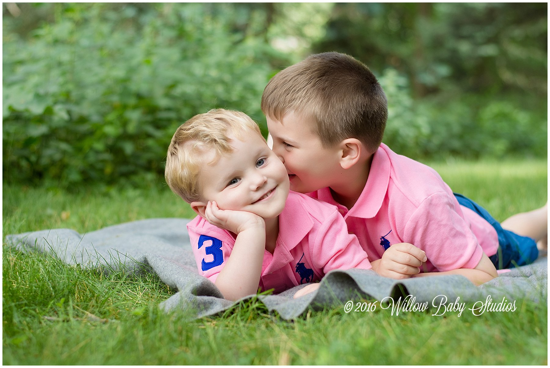 Young-brothers-laying-on-grass-telling-secrets