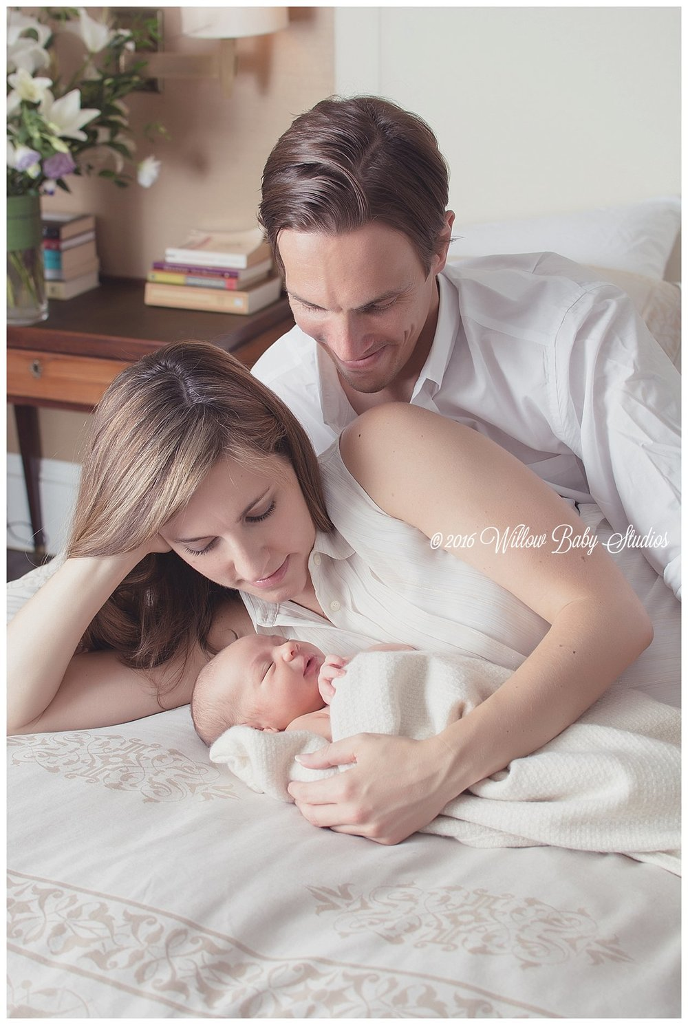 new-family-laying-on-bed-with-parents-gazing-lovingly-at-newborn