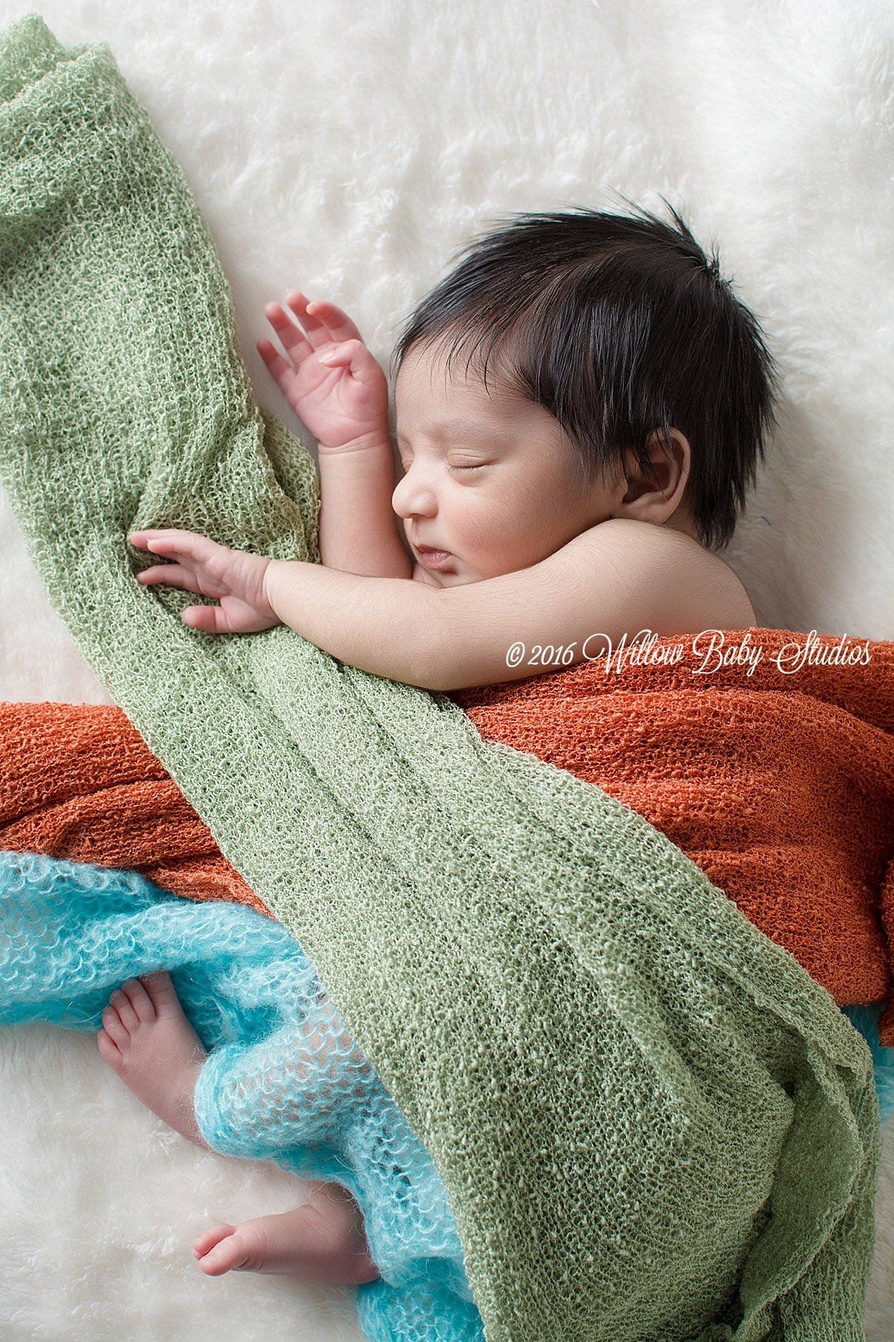 newborn-sleeping-on-side-wrapped-in-many-colored-swaddles