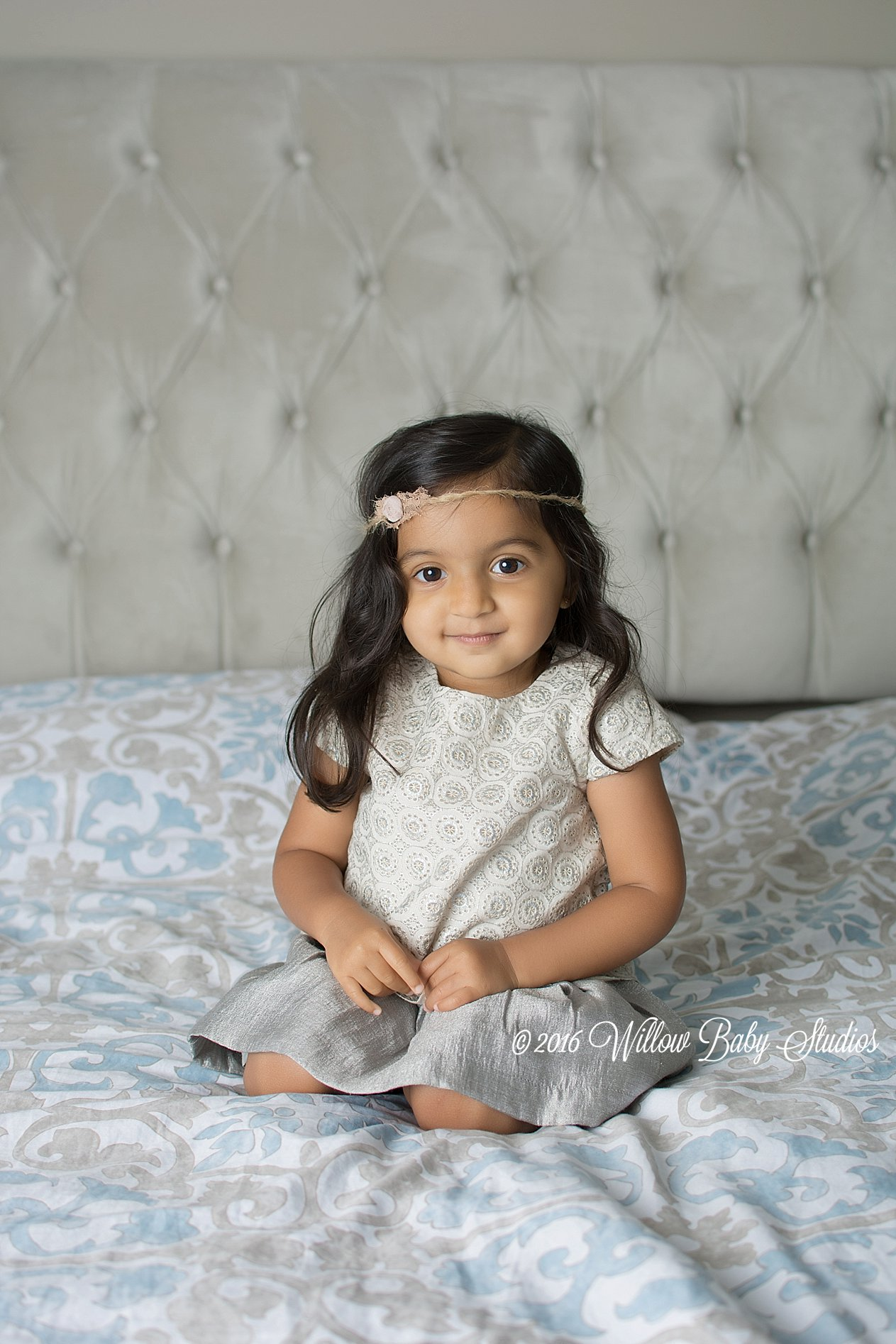 two-year-old-sitting-on-parents-bed-smiling-in-flower-headband