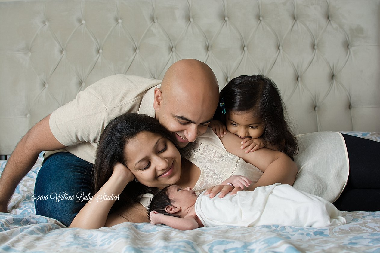 mom-dad-toddler-on-bed-peering-at-newborn